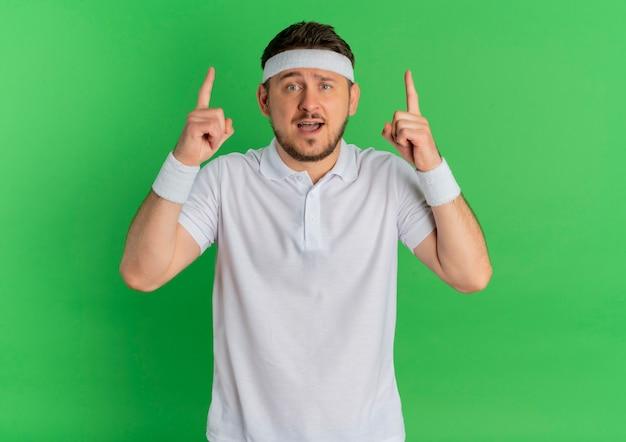 Młody fitness mężczyzna w białej koszuli z opaską skierowaną w górę palcami wskazującymi, patrząc do przodu, zaskoczony stojąc nad zieloną ścianą