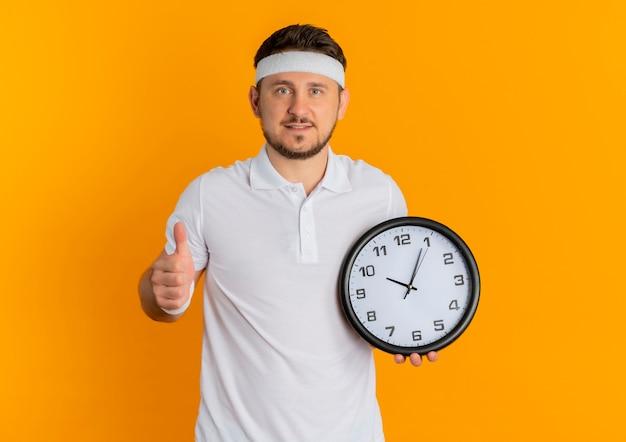 Młody fitness mężczyzna w białej koszuli z pałąkiem na głowę trzyma zegar ścienny pokazując kciuki do góry patrząc pewnie stojąc na pomarańczowym tle