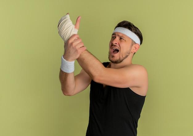 Młody fitness mężczyzna z opaską patrząc na jego zabandażowany nadgarstek cierpiący na ból stojąc na oliwkowym tle