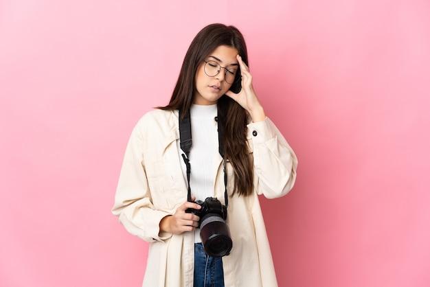 Młody fotograf brazylijska dziewczyna na białym tle na różowej ścianie z bólem głowy