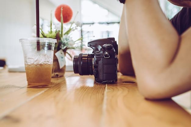 Młody fotograf czeka w kawiarni z kamerą.