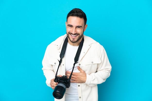 Młody fotograf człowiek na białym tle na niebieskiej ścianie dużo uśmiechnięty