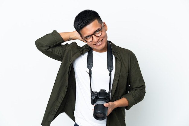Młody fotograf ekwadorski na białym tle na białej ścianie, śmiejąc się