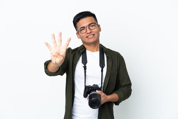 Młody fotograf ekwadorski na białym tle na białej ścianie szczęśliwy i licząc cztery palcami