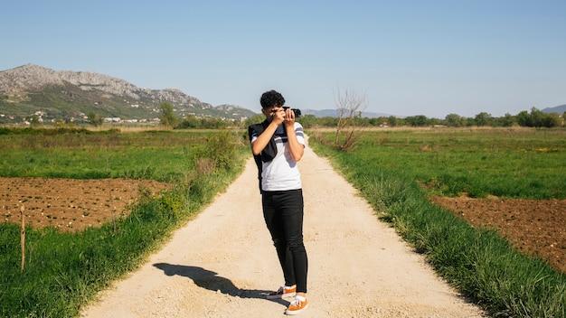 Młody fotograf fotografuje na zewnątrz