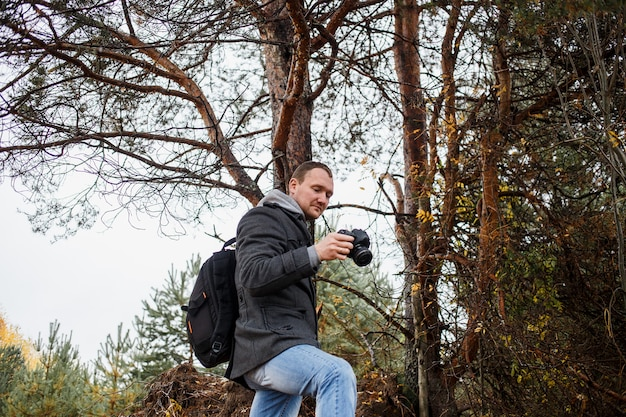 Młody fotograf fotografuje w jesień lesie