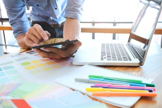 Młody fotograf i projektant grafiki w pracy w biurze biura.