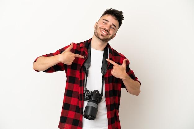 Młody fotograf kaukaski mężczyzna na białym tle dumny i zadowolony z siebie