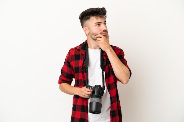 Młody fotograf kaukaski mężczyzna na białym tle mający wątpliwości i zdezorientowany wyraz twarzy