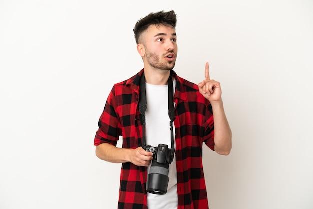 Młody fotograf kaukaski mężczyzna na białym tle myślący o pomyśle wskazującym palec w górę