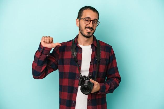 Młody fotograf kaukaski mężczyzna na białym tle na niebieskim tle czuje się dumny i pewny siebie, przykład do naśladowania.