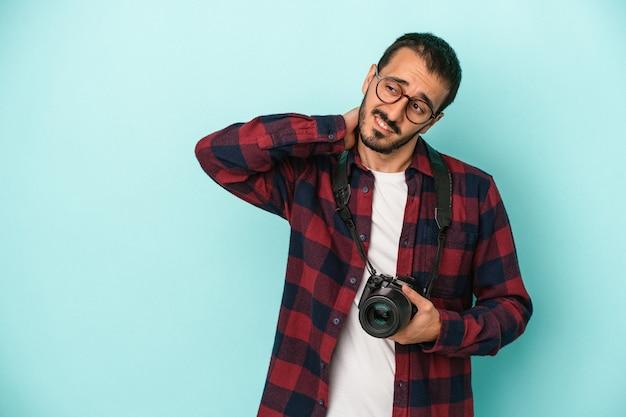 Młody fotograf kaukaski mężczyzna na białym tle na niebieskim tle dotykając tyłu głowy, myśląc i dokonując wyboru.