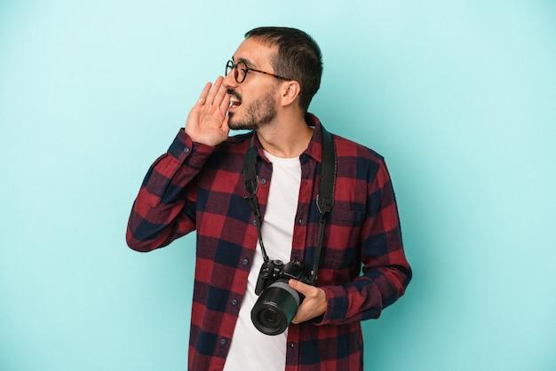 Młody fotograf kaukaski mężczyzna na białym tle na niebieskim tle krzycząc i trzymając dłoń w pobliżu otwarte usta.