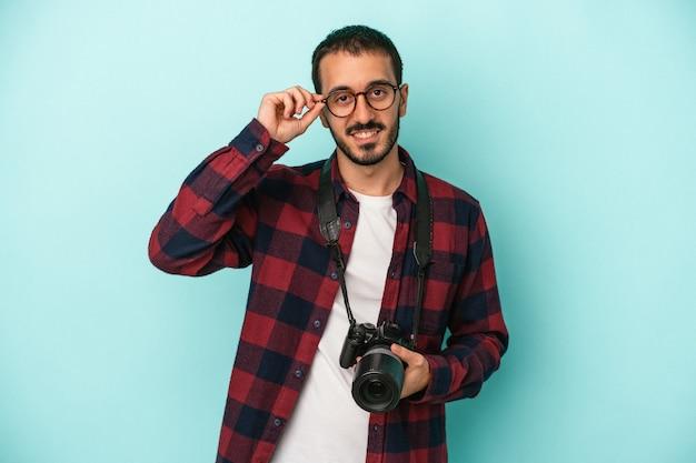 Młody fotograf kaukaski mężczyzna na białym tle na niebieskim tle podekscytowany utrzymanie ok gest na oko.