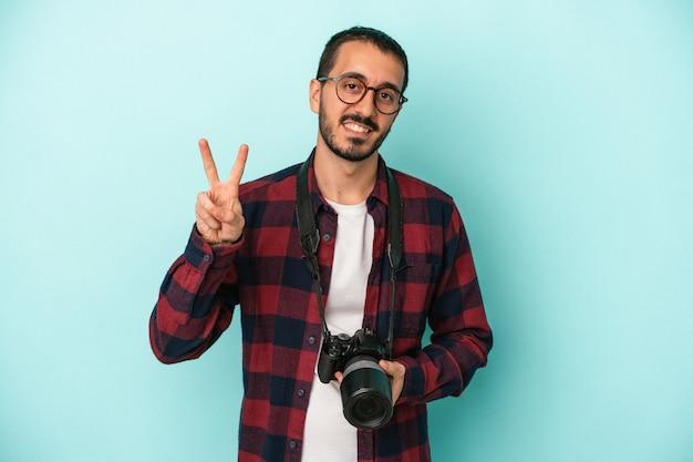 Młody fotograf kaukaski mężczyzna na białym tle na niebieskim tle pokazano numer dwa palcami.