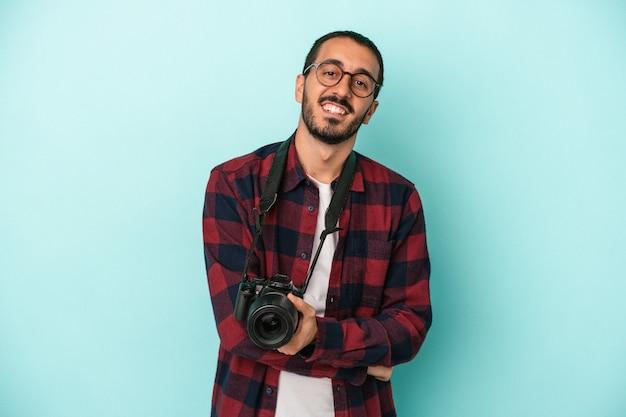 Młody fotograf kaukaski mężczyzna na białym tle na niebieskim tle śmiechu i zabawy.