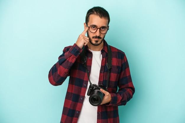 Młody fotograf kaukaski mężczyzna na białym tle na niebieskim tle wskazując świątynię palcem, myśląc, koncentruje się na zadaniu.