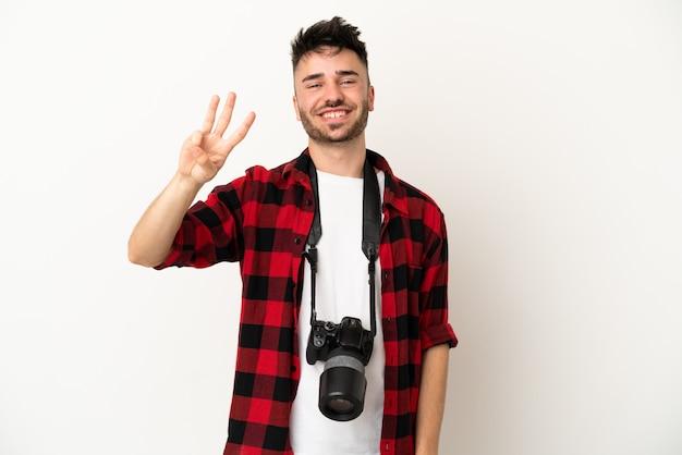 Młody fotograf kaukaski mężczyzna na białym tle szczęśliwy i liczący trzy palcami