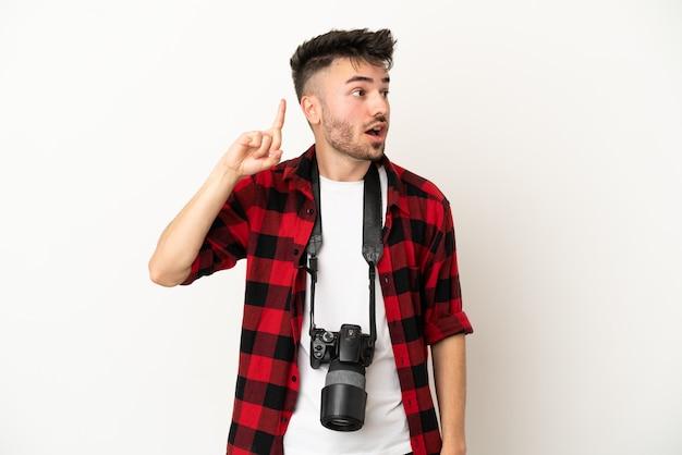 Młody fotograf kaukaski mężczyzna na białym tle zamierza zrealizować rozwiązanie, podnosząc palec w górę