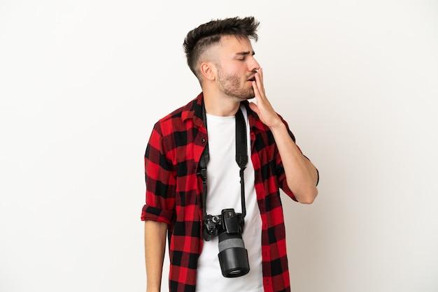 Młody fotograf kaukaski mężczyzna na białym tle ziewanie i zakrywanie szeroko otwartymi ustami ręką