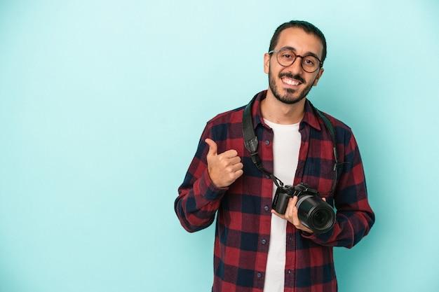 Młody fotograf kaukaski, odizolowany na niebieskim tle, uśmiechający się i podnoszący kciuk w górę