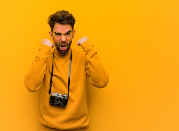 Młody fotograf mężczyzna krzyczy bardzo zły i agresywny