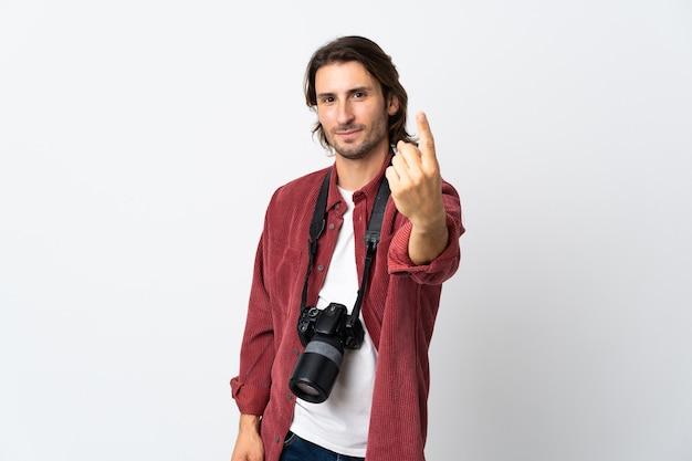 Młody fotograf mężczyzna na białym tle na białej ścianie robi nadchodzący gest