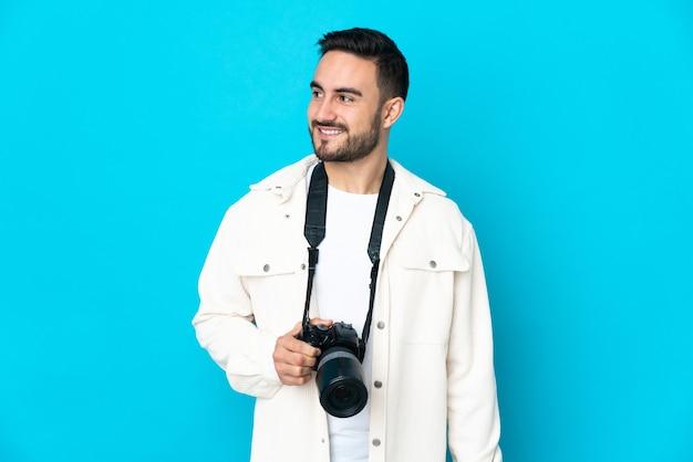Młody fotograf mężczyzna na białym tle na niebieskiej ścianie, patrząc z boku i uśmiechnięty