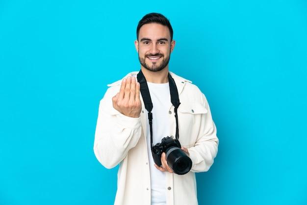 Młody fotograf mężczyzna na białym tle na niebieskiej ścianie, zapraszając do przyjścia z ręką