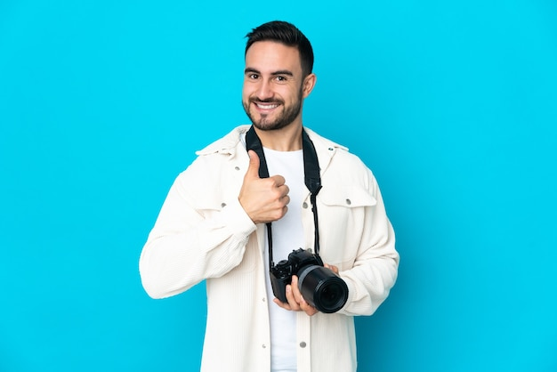 Młody fotograf mężczyzna na białym tle na niebieskim tle, dając kciuki do góry gestu