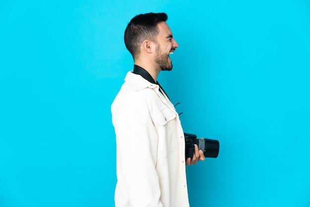 Młody fotograf mężczyzna na białym tle na niebieskim tle, śmiejąc się w pozycji bocznej