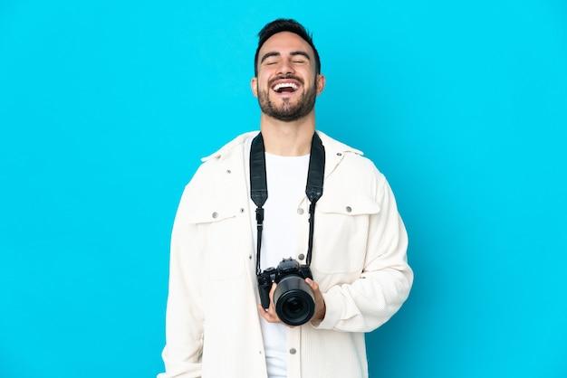 Młody fotograf mężczyzna na białym tle na niebieskim tle, śmiejąc się