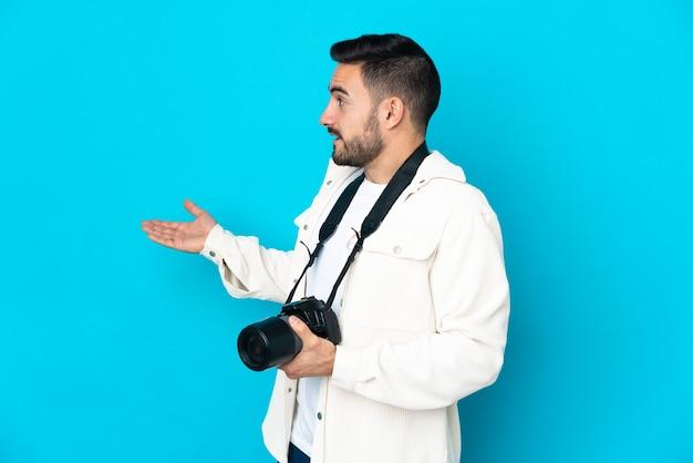 Młody fotograf mężczyzna na białym tle na niebieskim tle z wyrazem zaskoczenia, patrząc z boku