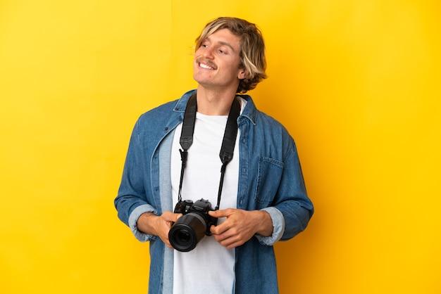 Młody fotograf mężczyzna na białym tle ooking w bok i uśmiechnięty