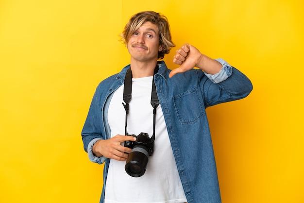 Młody fotograf mężczyzna na białym tle pokazując kciuk w dół z negatywną ekspresją