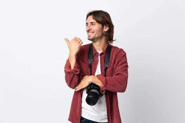 Młody fotograf mężczyzna na białym tle, wskazując na bok do przedstawienia produktu