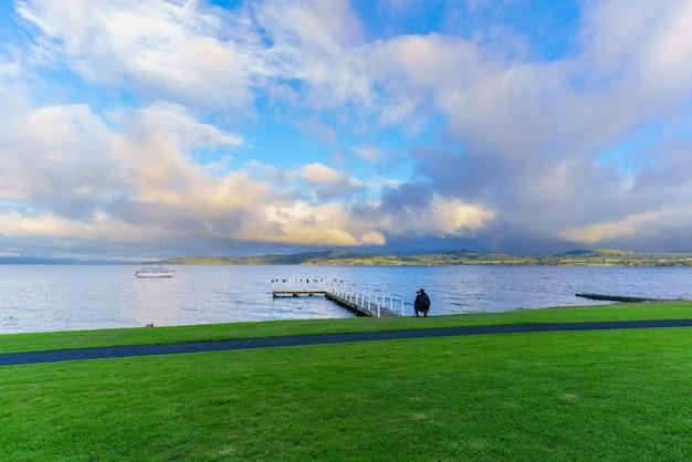 Młody fotograf mężczyzna robi zdjęcie rano jeziora taupo na wyspie północnej nowej zelandii