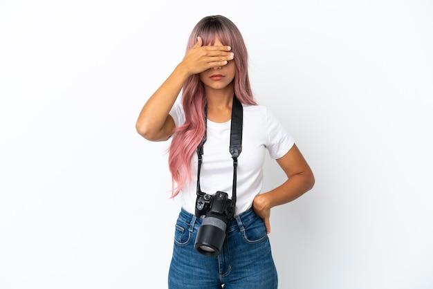 Młody fotograf mieszanej rasy kobieta z różowymi włosami na białym tle zasłaniając oczy rękami. nie chcę czegoś widzieć