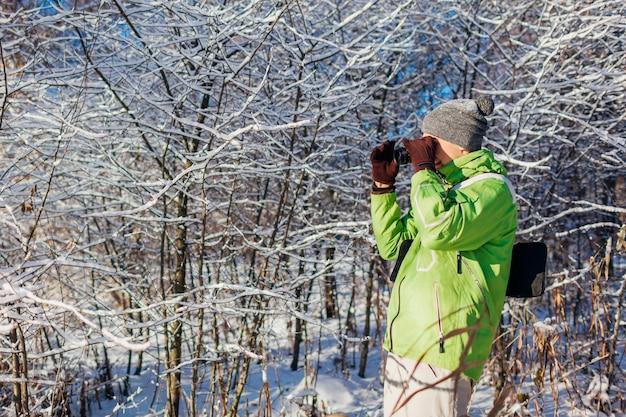 Młody fotograf robi zdjęcia zimowym lasem za pomocą aparatu. młody człowiek fotografowania na zewnątrz