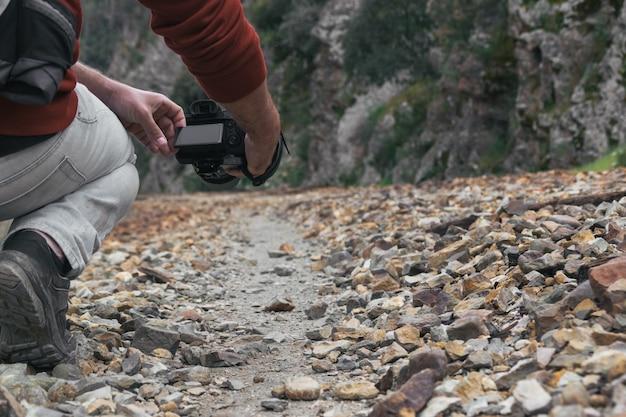 Młody fotograf robiący zdjęcie aparatem na kamiennej ścieżce, dawniej torze kolejowym.