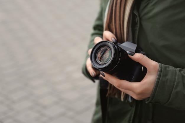 Młody fotograf z aparatem, na zewnątrz
