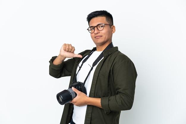 Młody fotograf z ekwadoru na białej ścianie dumny i zadowolony z siebie
