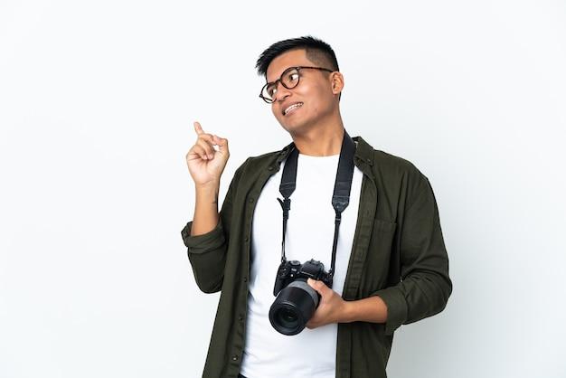 Młody fotograf z ekwadoru na białym tle, który zamierza realizować rozwiązanie, podnosząc palec w górę
