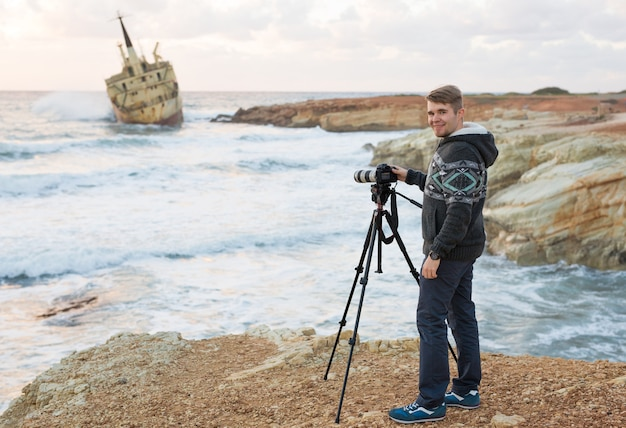 Młody fotograf z plecakiem robiąc aparatem zdjęcia morza i skał.