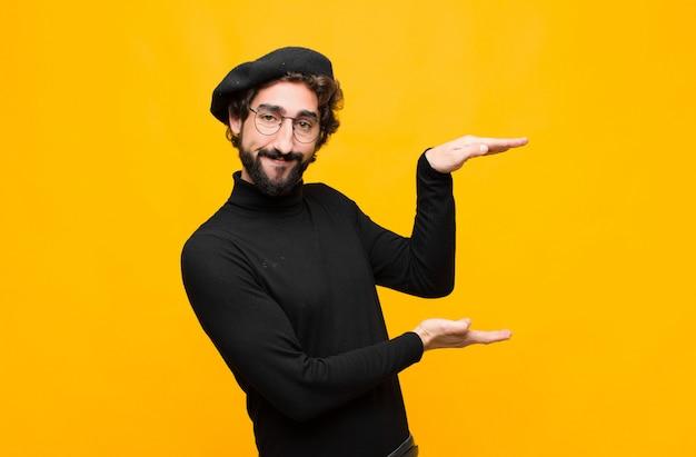 Młody francuski artysty mężczyzna trzyma przedmiot obiema rękami na stronie kopii przestrzeni, pokazuje, oferuje lub reklamuje przedmiot nad pomarańczową ścianą