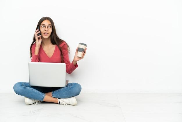 Młody francuski dziewczyna siedzi na podłodze ze swoim laptopem, trzymając kawę na wynos i telefon komórkowy
