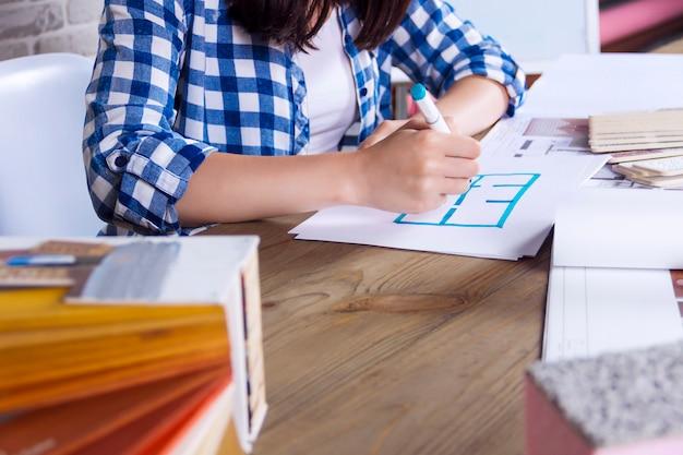 Młody freelancer, projektant wnętrz, pracuje nad nowym projektem mieszkania w studio projektowym. kobiety dziewczyny spotkanie kobiet z biurkiem spotkać z pin up szkice rysunki i szkice nowego projektu
