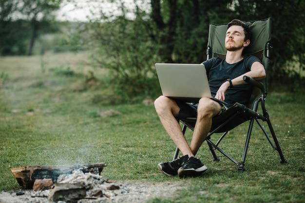 Młody freelancer relaks w lesie. człowiek pracuje na laptopie na naturze. praca zdalna, aktywność na świeżym powietrzu latem. podróże, turystyka, technologia, turystyka, koncepcja ludzi - mężczyzna siedzi na krześle na zewnątrz.