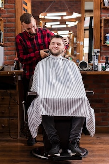 Młody fryzjer i klient uśmiecha się