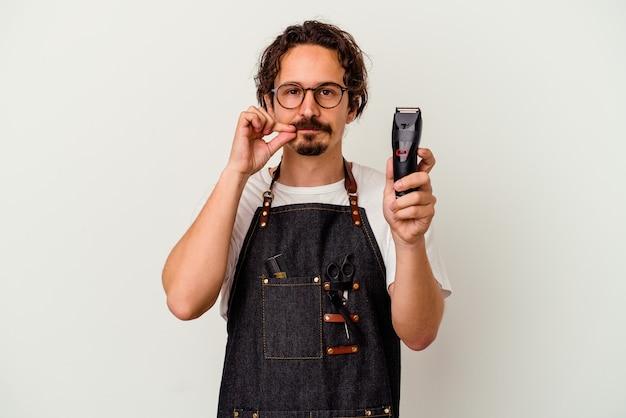 Młody fryzjer kaukaski mężczyzna na białym tle biały z palcami na ustach, zachowując tajemnicę.